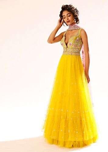 A women having a short hair posing for a photo wearing Sun Yellow Anarkali Suit by Kalki Fashion